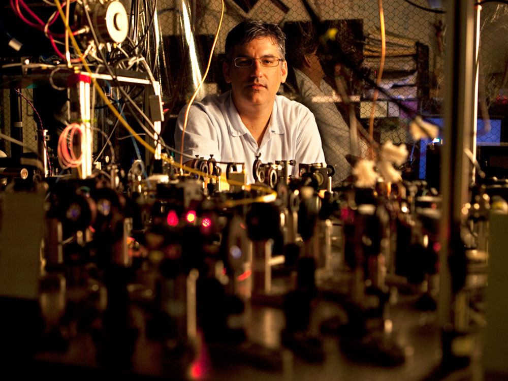 Chris Monroe sits behind an optics table filled with experimental pieces of his ion trapping quantum computing technology.